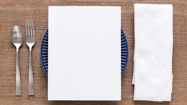 Endecha plana de papel de menú en blanco en un plato con cubiertos y servilletas