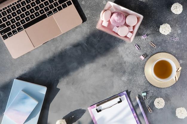 Endecha plana de papelería de oficina con taza de té con malvavisco y portátil sobre un fondo gris con sombras.