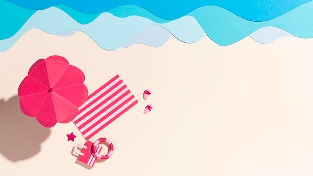 Endecha plana de paraguas de verano junto a la toalla