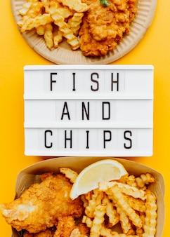 Endecha plana de pescado y patatas fritas con caja de luz y salsa