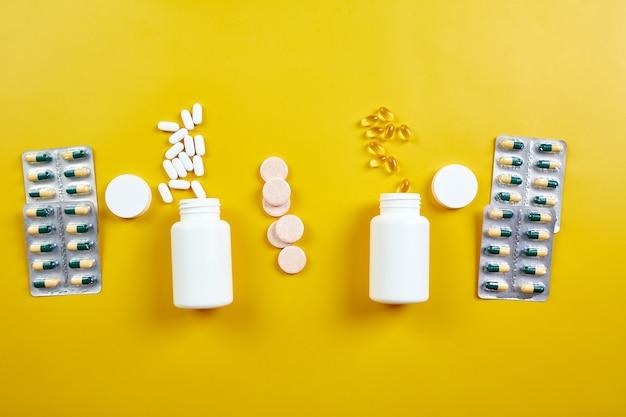 Endecha plana de píldoras vitaminas de aceite de pescado sobre fondo amarillo concepto de salud suplementos alimenticios saludables