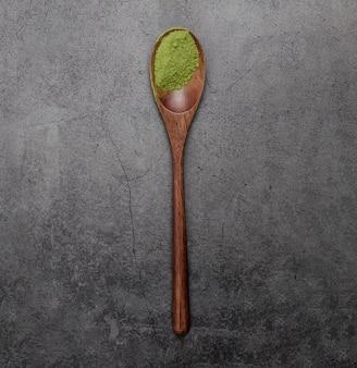 Endecha plana de polvo de té matcha en cuchara de madera