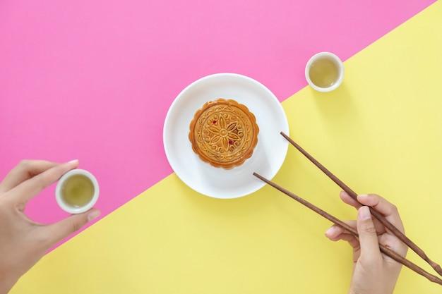 Endecha plana del postre del festival chino, pastel de luna sobre fondo colorido con tés y chuletas