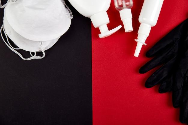 Endecha plana de protección contra coronavirus, máscaras de protección médica, guantes, frascos desinfectantes para manos, antiséptico, desinfección, spray sobre fondo rojo negro, copia espacio