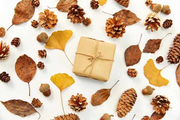 Endecha plana de un regalo en medio de una corona hecha de hojas de otoño y conos de coníferas