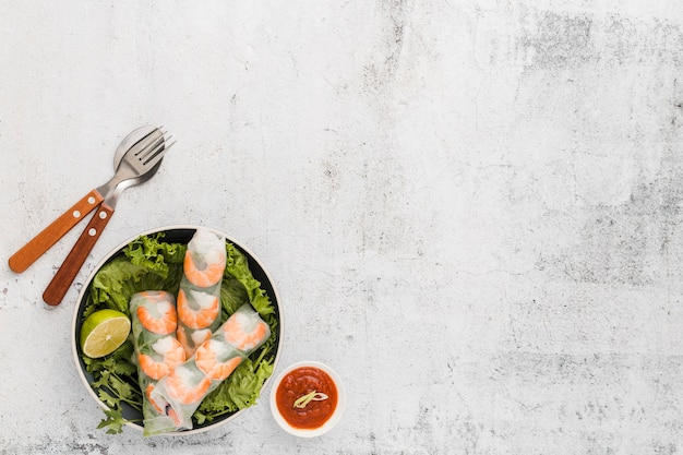 Endecha plana de rollos de camarones frescos en un tazón con salsa