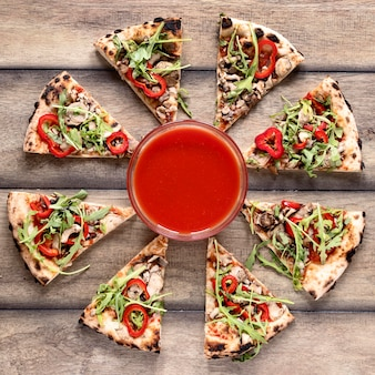 Endecha plana sabrosa pizza sobre fondo de madera
