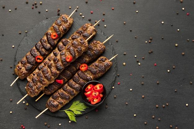 Endecha plana de sabroso kebab con condimentos en placa