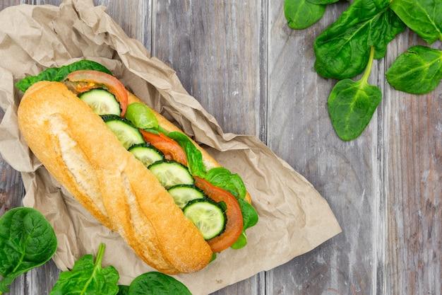Endecha plana de sándwich con rodajas de espinacas y pepino
