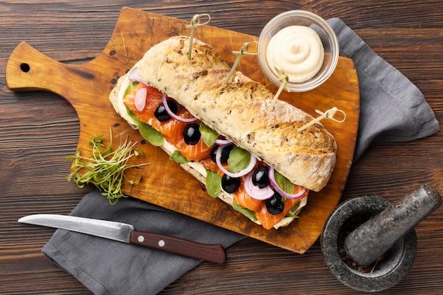 Endecha plana de sándwich de salmón con cubiertos