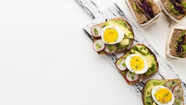 Endecha plana de sándwiches de huevo y aguacate con espacio de copia