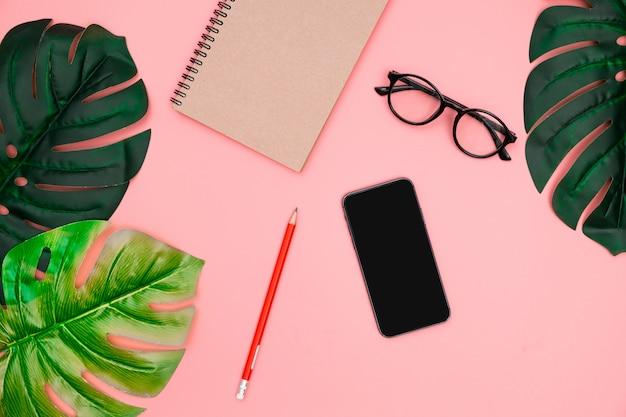Endecha plana con smartphone, cuaderno, hojas de palmera tropical monstera sobre fondo rosa