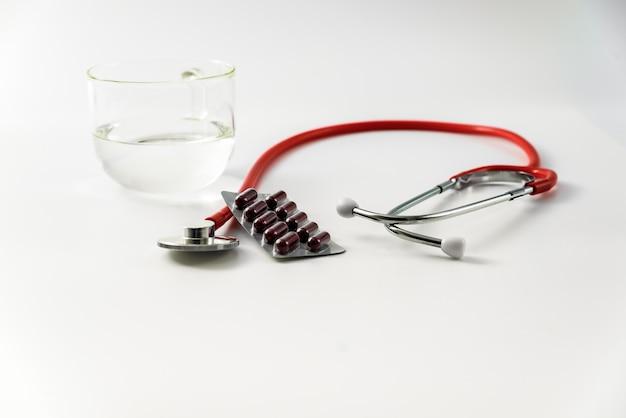 Endecha plana sobre fondo blanco, analgésicos con un vaso de agua recetados por un médico.