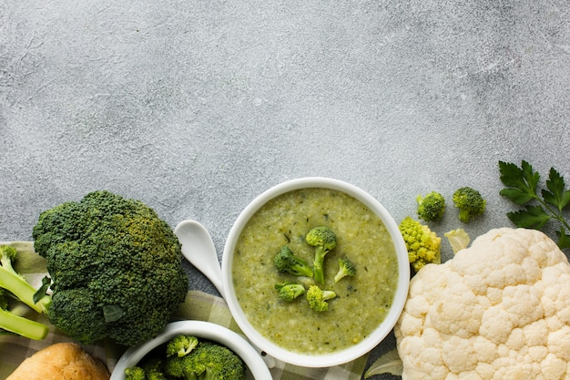 Endecha plana, sopa de brócoli y coliflor en un tazón con espacio de copia