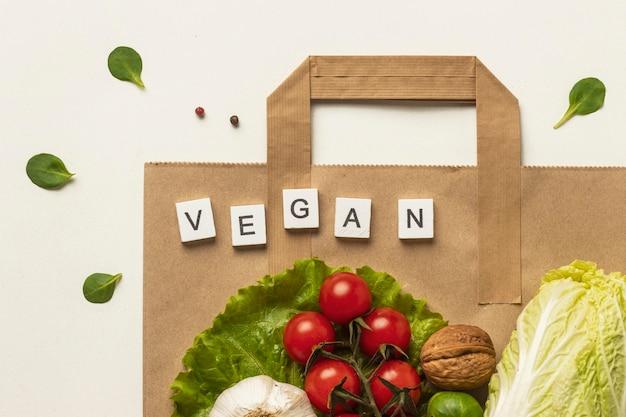 Endecha plana de surtido de verduras con bolsa de papel y la palabra vegana