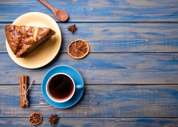 Endecha plana de taza de té y rebanada de pastel