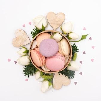 Endecha plana de tazón con macarons y rosas