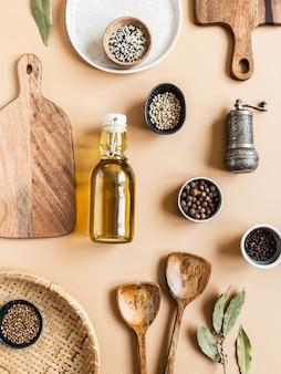Endecha plana de tazones pequeños, varias especias secas, utensilios de cocina de madera, aceite de oliva en botella de vidrio.