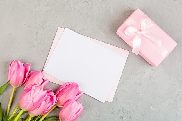 Endecha plana con tulipanes y caja de regalo con espacio de copia en gris
