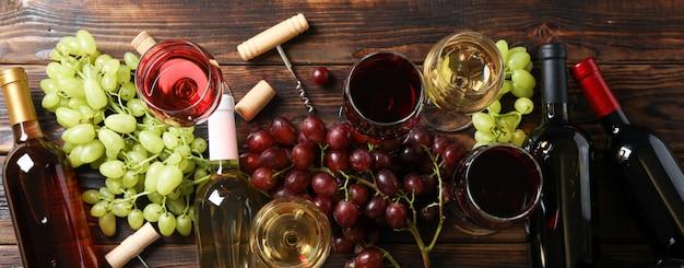 Endecha plana. uvas, sacacorchos, botellas y vasos con vino en madera