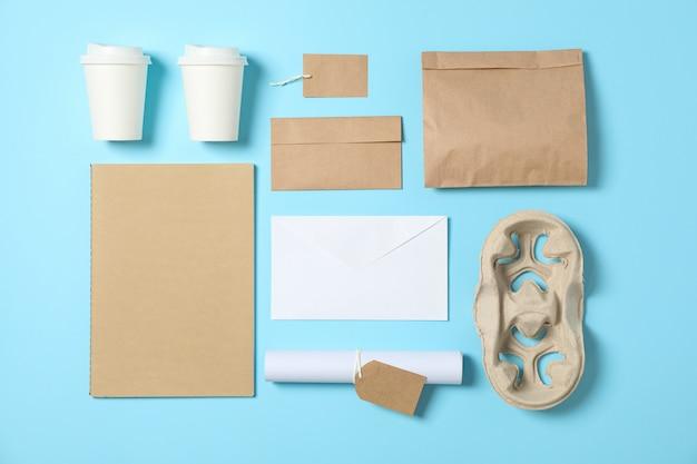 Endecha plana. vasos de papel y suministros de oficina sobre fondo azul, espacio de copia