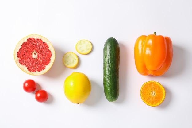 Endecha plana con verduras y frutas en blanco, espacio para texto