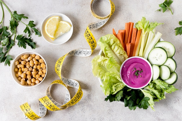 Endecha plana de verduras con garbanzos y cinta métrica
