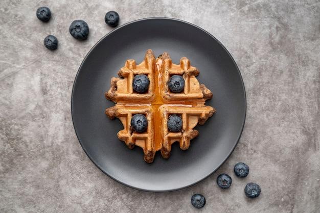 Endecha plana de waffle en plato con arándanos