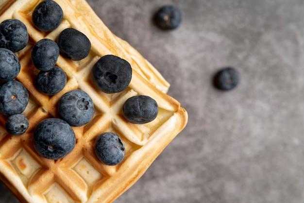 Endecha plana de waffles apilados con arándanos en la parte superior