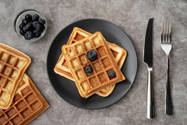 Endecha plana de waffles en un plato con arándanos y cubiertos