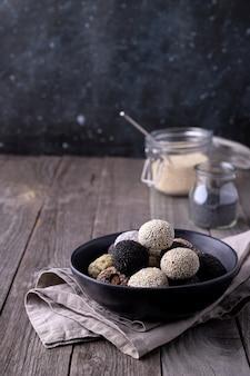 Energía cruda muerde bolas preparadas con ingredientes naturales sobre fondo de madera rústica antigua
