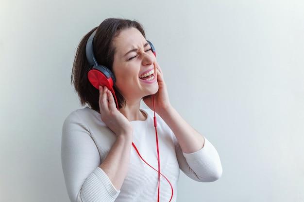 Energía joven morena dama mujer escuchando música en auriculares y cantando aislado en blanco