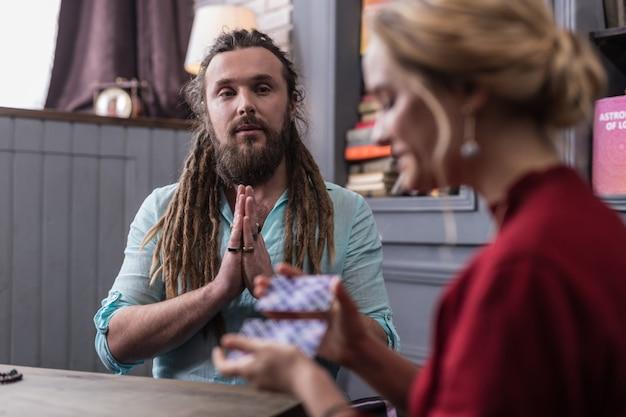 Energía mágica. buen hombre guapo juntando sus manos mientras tiene una sesión de adivinación