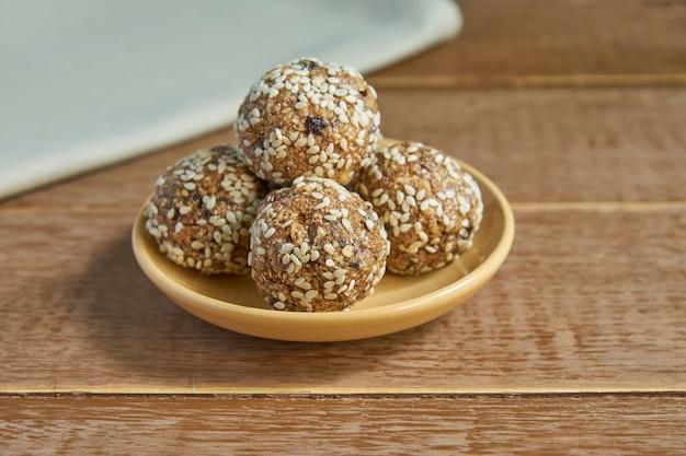 La energía orgánica saludable granola pica con nueces, cacao, ciruelas pasas, sésamo y miel. refrigerio crudo vegano y vegetariano en madera