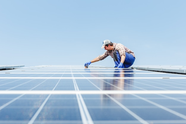 Energía del panel solar. el hombre del ingeniero eléctrico está trabajando en la estación solar en el techo contra el cielo azul con equipo. desarrollo de tecnología de energía alternativa solar. concepto ecológico.