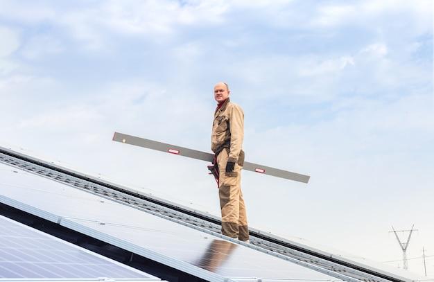 Energía del panel solar. el hombre del ingeniero eléctrico está trabajando en la estación solar en el techo contra el cielo azul mediante la verificación del nivel del equipo. desarrollo de tecnología de energía alternativa solar. concepto ecológico.