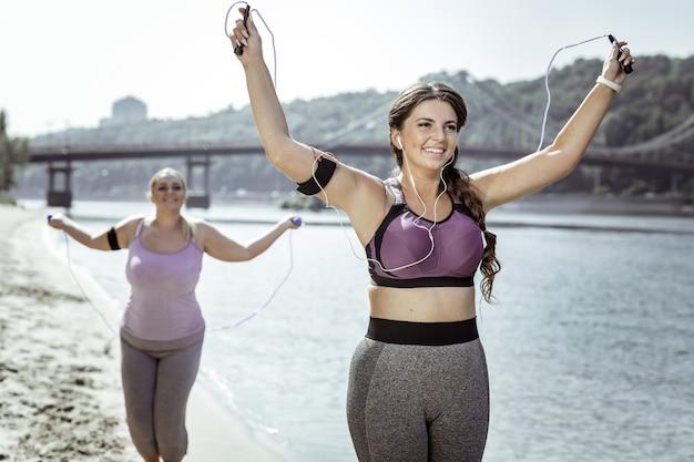Energía positiva. mujeres bonitas felices sosteniendo cuerdas en sus manos mientras hacen ejercicio en la playa