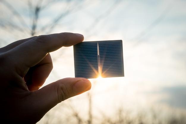 Energía verde, célula solar fotovoltaica con mano.