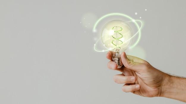 Energía verde con mano sosteniendo un fondo de bombilla ambiental