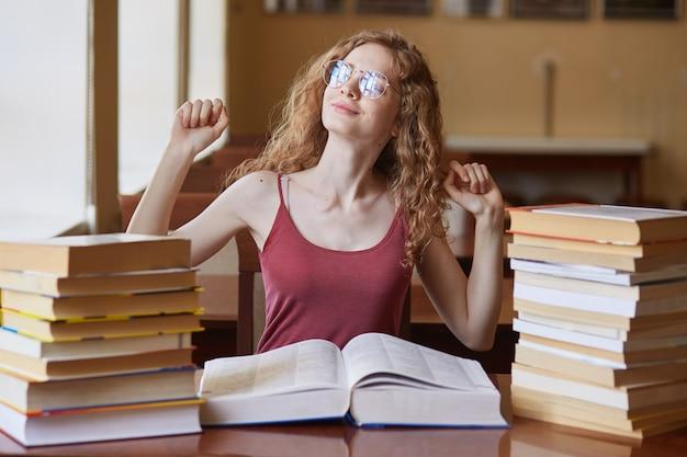 Enérgica y atractiva estudiante linda que se estira después de sentarse en una silla durante un largo período de tiempo