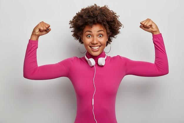 Enérgica y poderosa dama afroamericana levanta los brazos para mostrar músculos y fuerza, sonríe ampliamente, usa audífonos estéreo alrededor del cuello