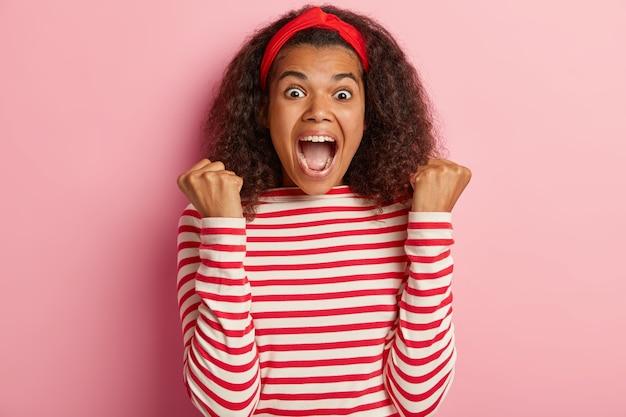 Energizada adolescente con pelo rizado posando en suéter rojo a rayas
