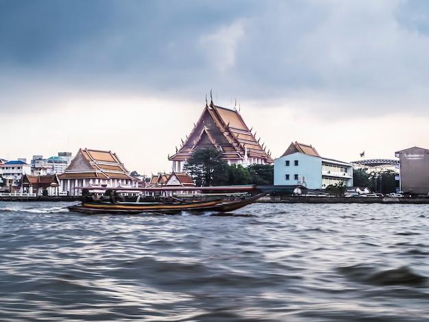 Enero de 2019, bangkok, tailandia, el río de bangkok y el edificio rascacielos rascacielos paisaje urbano paisaje fluvial taxi barco sirven para el transporte público fondo del templo de la ciudad vieja