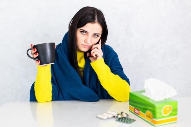 Enferma joven cubierta con una manta sosteniendo una taza de té sentado en la mesa