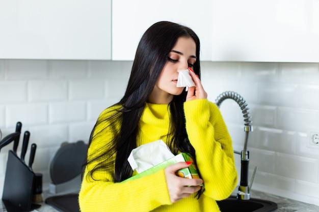 Enferma joven se sopla la nariz en la cocina.