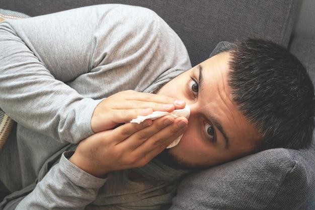 Enfermedad. anímate en casa. un joven está enfermo, recibe tratamiento en casa. se sopla la nariz en una servilleta, secreción nasal. infección, epidemia, portador de bacilo