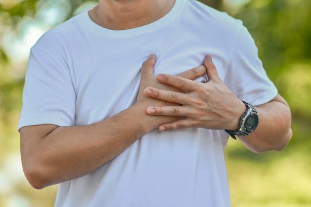 La enfermedad cardíaca del hombre mayor sostiene su mano en su corazón mientras hace ejercicio. problemas de salud del corazón