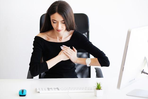 Enfermedad cardíaca de la mujer de negocios que ella está trabajando en una oficina.