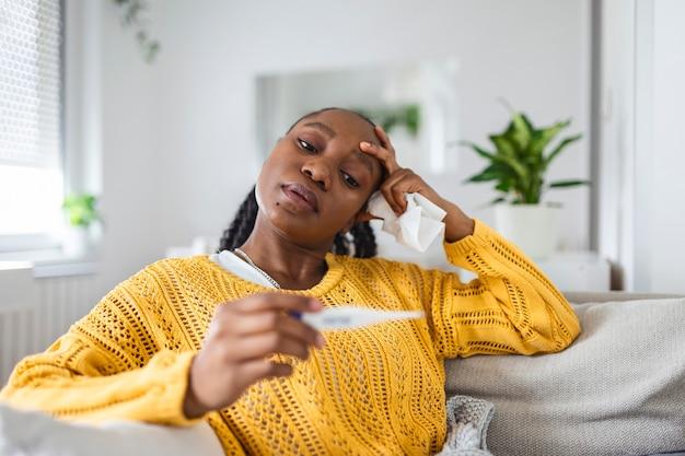 Enfermedad, concepto de problema de virus estacional. mujer enferma con gripe acostada en la cama mirando la temperatura en el termómetro. mujer enferma acostada en la cama con fiebre alta. coronavirus de la gripe fría, covid19