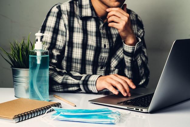 Enfermedad por coronavirus o concepto de protección covid-19: el hombre joven trabaja en la oficina en casa con equipo de protección y limpieza para protegerse contra el virus de la corona mientras usa una computadora portátil en el escritorio